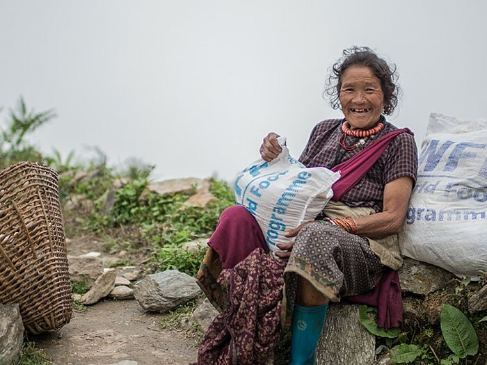 A woman holds her WFP rice and lentils sacks after the food distribution
