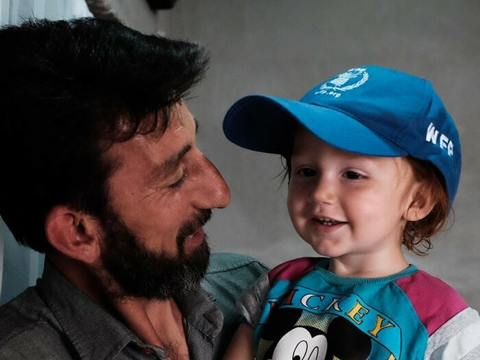 man with child in WFP cap