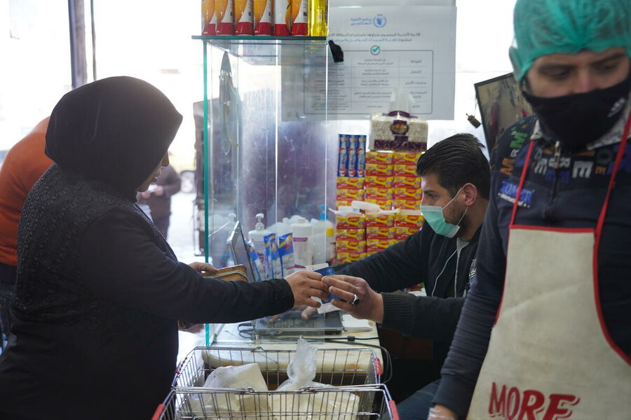 Woman pays with WFP card at a store in Syria